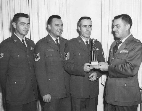 Sembach Air Base Commander Col. D. Brawner accepts trophy from the Sembach Rifle/Pistol team. Left to right: SSgt Dale Mellinger, MSgt Hendershot and MSgt. James Cazel.